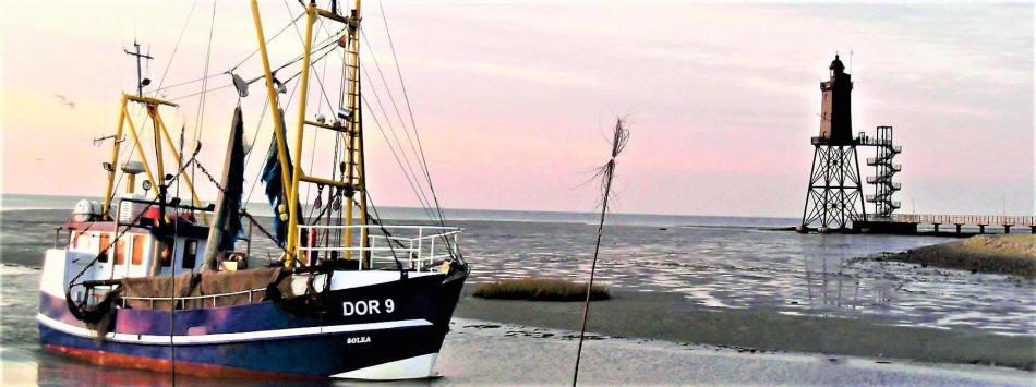 Kutter fährt in die Hafeneinfahrt ein. Im Hintergrund der Leuchtturm Eversand